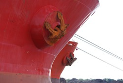 low angle view of the bow of a red shipping tanker anchored in port