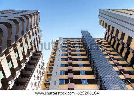 low angle view of the common modern condominium building with skyscrapers over blue sky, concept of economics, construction, modern city life, accommodation etc.