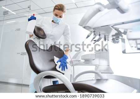 Low angle view of the female blonde dentist carefully sterilize the medical armchair inside a dental clinic during the coronavirus pandemic. Working during pandemic concept. Stock photo Сток-фото ©