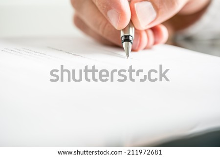 Low angle view of the fingers of a man writing on a document with a fountain pen conceptual of communication, correspondence, business agreement, legal contract or creativity.