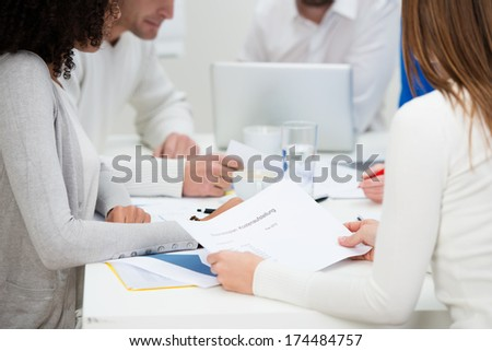 Low angle view of the hands and paperwork on the table of a group of business colleagues in a meeting as they have a brainstorming session