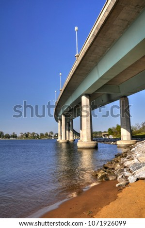 Low angle view of the Naval Academy Bridge from the sandy shore of the Severn River in Annapolis, Maryland. Concrete pillars or piers rise out of the river to support the bridge as it curves west. #1071926099