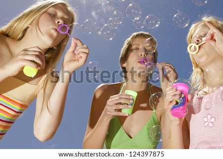 Low angle view of three happy children at a party standing in a semicircle blowing bubbles from plastic hoops