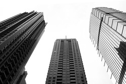 Low angle view of three skyscrapers  with bright sky on the background in black and white
