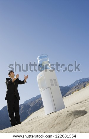 Low angle view of tired businessman looking at water cooler in the desert