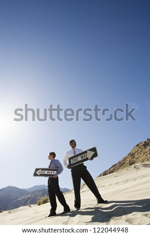 Low angle view of two businessmen standing with sign board in opposite direction at desert