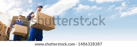 Low Angle View Of Two Young Delivery Man Carrying Cardboard Box In Front Of Truck