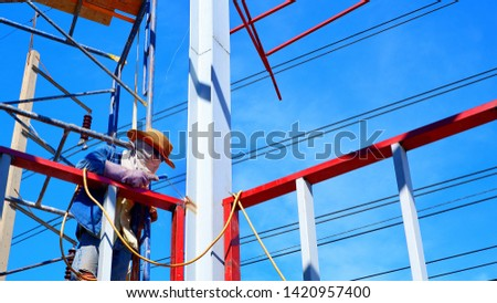 Low angle view of veiled welder in blue jean with hat and sunglasses on scaffolding is welding metal building structure with electric pole and power lines against blue sky background  #1420957400