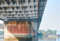 Low angle view of Vivekananda Setu or Bally Bridge (a multispan steel bridge) from a river boat beneath the bridge. View of girders and concrete pillar supporting the bridge on Hooghly river.