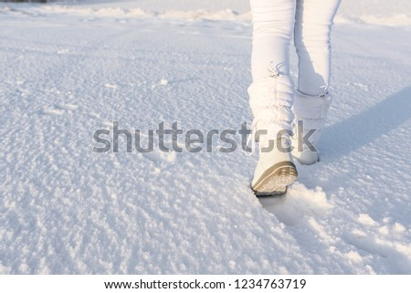 Low angle view of walking away female legs with white snow boots on, in deep snow. Winter background. #1234763719