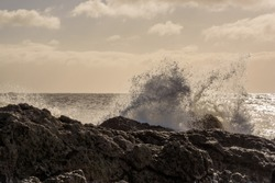 Low angle view of waves breaking over rocks and spray.