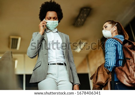 Low angle view of women with protective masks passing by each other while walking at airport terminal during virus epidemic.
