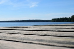 Low angle view of wooden pier. Lake on background. Shallow depth of field.