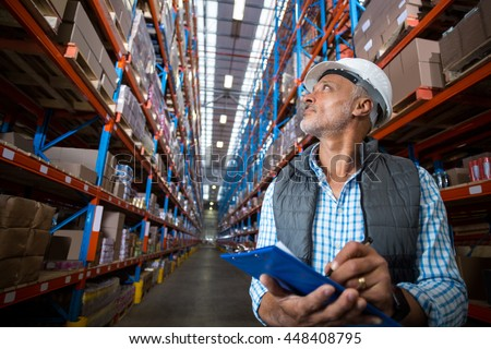 Low angle view of worker is looking up and holding a clipboard in a warehouse #448408795