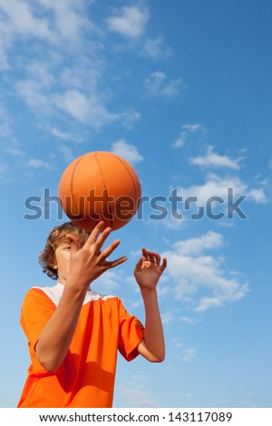 Low angle view of young basketball player spinning ball against sky