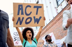 Low angle view of young black woman holding act now sign and shouting while taking a part in demonstrations on city streets.