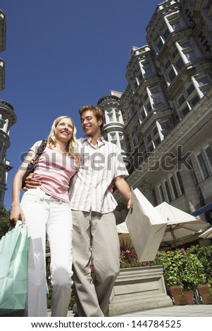 Low angle view of young couple walking down city street with shopping bags