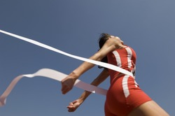 Low angle view of young female athlete crossing finish line against clear blue sky