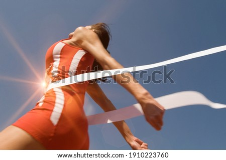 Low angle view of young female athlete crossing finish line against clear blue sky Stock photo ©