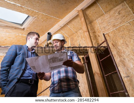 Low Angle View of Young Male Architect and Construction Worker Foreman Consulting Building Plans Inside Unfinished House with Exposed Particle Plywood Boards