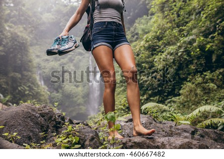 Low angle view of young woman walking down the mountain barefoot. Female hiker walking barefoot on rock with waterfall in background. ストックフォト ©