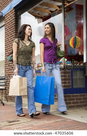 Low angle view of young women walking down a sidewalk lined with retail stores. They are both carrying shopping bags. Vertical shot.