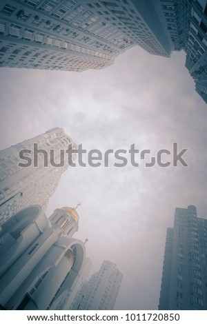 Low angle view on small orthodox church among modern high multi-storey residential buildings. Frosty foggy morning at city street. Kiev. Ukraine.