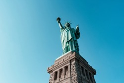 Low angle view on Statue of Liberty National Monument, New York, USA. Famous colossal copper sculpture standing on stone pedestal know as world symbol of freedom. View against blue cloudless sky.