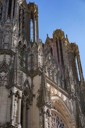 Low-angle view on the 82-meter high, twin symmetric towers of Notre-Dame Cathedral of Reims, in the Northeast of France ; the Gothic architecture features complex elements and a rich statuary