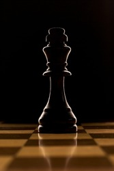 Low angle view over a reflective chessboard of a backlit chess piece - the king - against a dark background