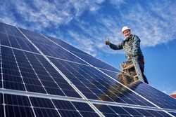 Low angle view portrait of a smiling worker, installing solar batteries, who is standing on ladder at solar plant against blue sky, showing thumb up. Concept of alternative sources of energy.