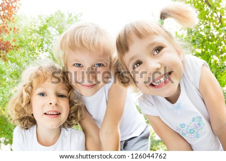 Low angle view portrait of happy children playing outdoors in spring park. Fisheye shot - stock photo