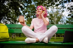 Low angle view portrait of pretty cheerful girl sitting on bench listening hit single drinking latte on fresh air in forest outdoors