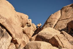 Low angle view to giant inselbergs in Joshua Tree National Park. Rocky outcrop with deep blue sky background