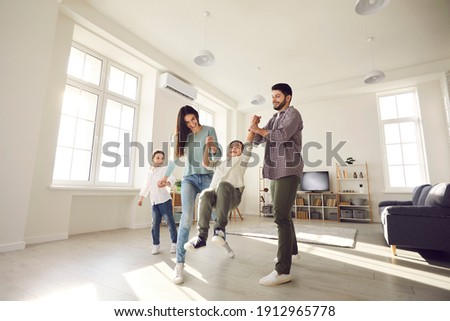 Low angle wide shot happy family with kids playing together at home. Young couple with little children enjoying free time and having fun in light spacious living-room of new house or rented apartment
