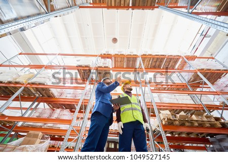 Low angle wide shot of mature businessman talking to warehouse worker, discussing stock inventory standing against tall shelves, copy space