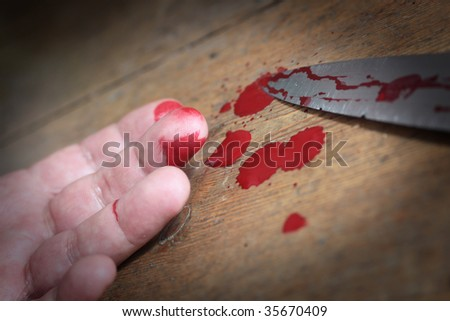 Low angled up close image of a bloodied hand and knife with blood splatters set on a wooden floor background.