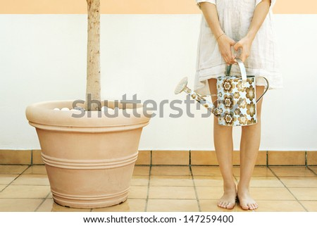 Low body section of a young woman standing on a roof terrace next to a tree plant pot, holding a full watering can while doing her gardening and tending her plant.