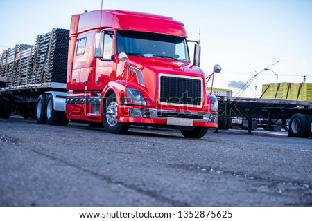 Low cab for decrease in resistance to oncoming air flow bright red big rig bonnet semi truck with loaded flat bed semi trailer standing on the parking lot in row with another semi trucks