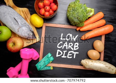 Low carb diet on chalkboard, health conceptual. Healthy fresh low carbohydrates food; egg, fish, lemon, tomatoes, apple, carrot and broccoli with dumbbell and measuring tape. #707974792