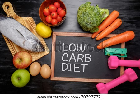Low carb diet on chalkboard, health conceptual. Healthy fresh low carbohydrates food; egg, fish, lemon, tomatoes, apple, carrot and broccoli with dumbbell and measuring tape. #707977771