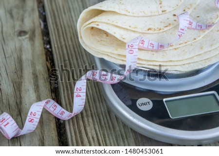 Low carb tortillas on a food scale with measuring tape on wooden background. Blank empty room for text or copy space. Healthy health food trend for keto and low-carb diets. Plain tortilla, high fiber. #1480453061