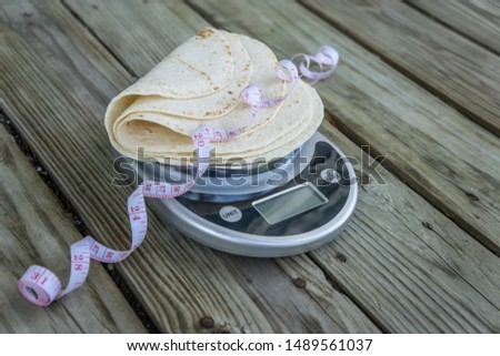 Low carb tortillas on a food scale with measuring tape on wooden background. Blank empty room for text or copy space. Healthy health food trend for keto and low-carb diets. Plain tortilla, high fiber. #1489561037