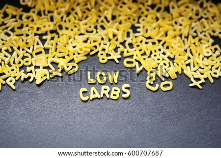 Low carbs phrase spelled with raw letter-shaped pasta on blackboard background #600707687