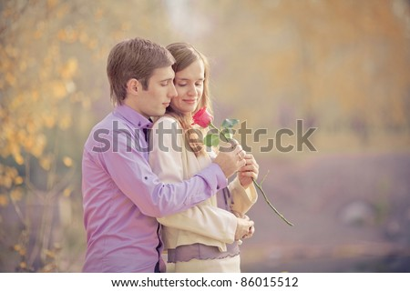 low contrast image of a happy young couple spending time outdoor in the autumn park (focus on the man)