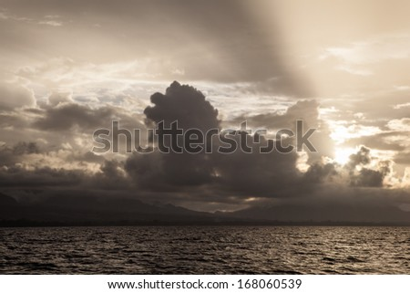 Low cumulous clouds are illuminated by the last light of the day in the Solomon Islands. This region is part of the Coral Triangle, the most diverse area in the world for marine organisms. #168060539