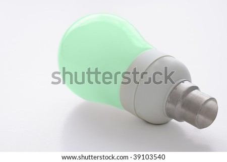"Low energy consumption light bulb, isolated against a white background. Green glass symbolizing ""green"" energy and environmentally friendly"