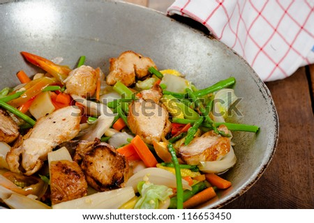 low fat asian vegetable dish with chicken in a wok on wooden table