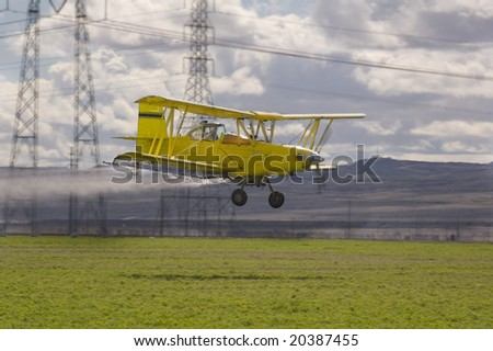 Low flying crop spraying aircraft