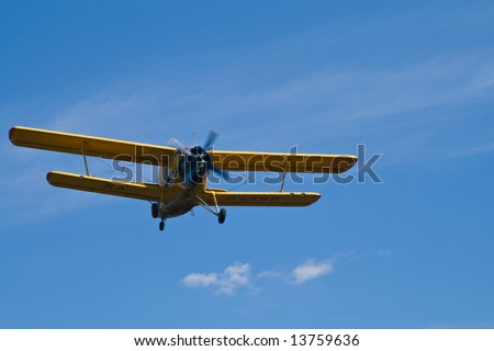 Low flying yellow biplane on blue sky